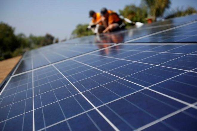 Solar Technicians Install Solar Panels On The Roof Of A Hous